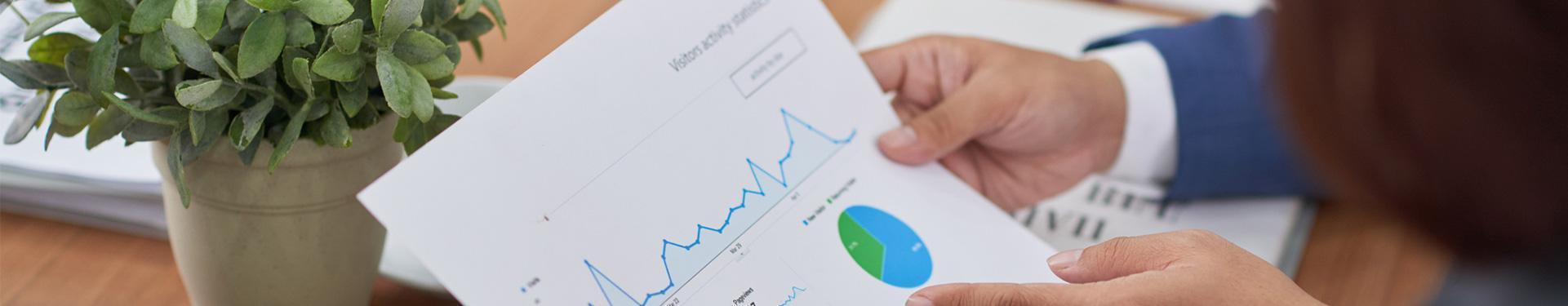 Mężczyzna z kartką papieru ze statystykami w ręku